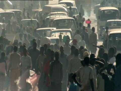 ws crowd of pedestrians and bystanders on dusty, busy street with traffic / kigali, rwanda - キガリ点の映像素材/bロール