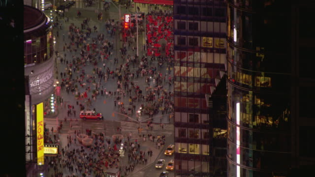 A crowd of pedestrians gather in Times Square at night.