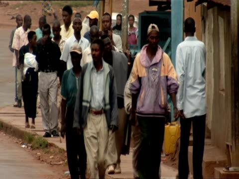 ms crowd of pedestrians walking on sidewalk of busy street in nyamirambo / nyamirambo, kigali, rwanda - ルワンダ点の映像素材/bロール