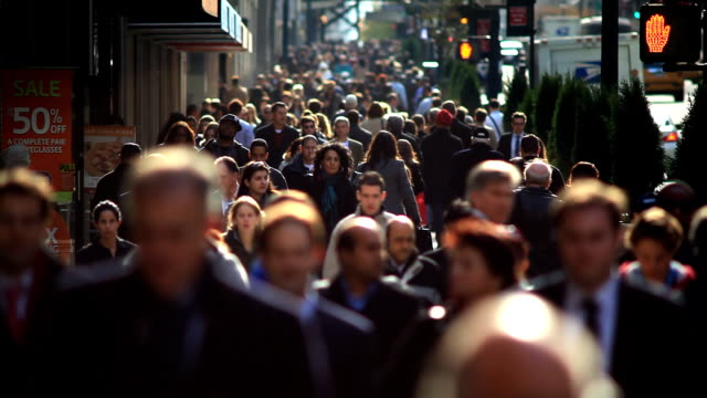 A crowd of pedestrians walks along a busy street in New York City.