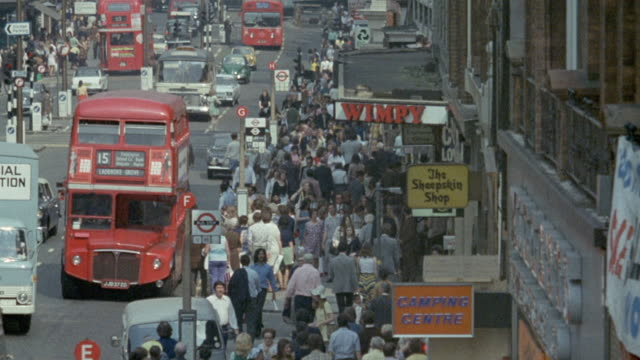 1971 montage crowd of people and traffic on a busy city street / united kingdom - high street stock videos & royalty-free footage