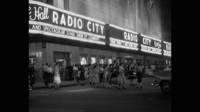 vidéos et rushes de crowd of people and traffic outside radio city music hall, rockefeller center, midtown manhattan, new york city, new york state, usa - panneau commercial
