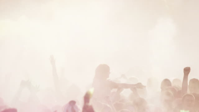crowd of people at a Hindu festival throwing colored powder into the air