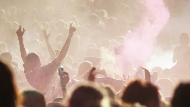 vídeos de stock, filmes e b-roll de crowd of people at a hindu festival throwing colored powder into the air and dancing - jogando se na multidão