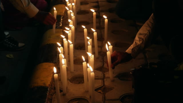 A crowd of people burning and placing candles on a footpath