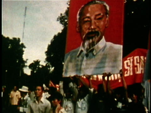Crowd of people carrying banners and large iconic portrait of Ho Chi Minh / Vietnam