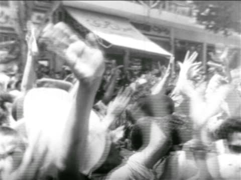 b/w 1956 crowd of people cheering waving outdoors / egypt / suez crisis / newsreel - menschlicher arm stock-videos und b-roll-filmmaterial