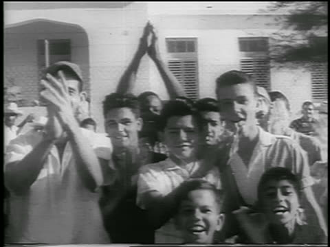 b/w 1959 crowd of people clapping outdoors / postrevolution havana / newsreel - 1959 stock-videos und b-roll-filmmaterial