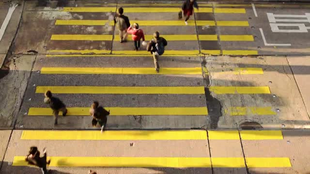 stockvideo's en b-roll-footage met crowd of people crossing on the yellow pedestrian lane in hong kong on a sunny day - timelapse - hong kong