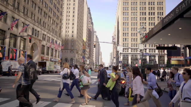 crowd of people crossing street in new york city. commuters walking in business district. cityscape background