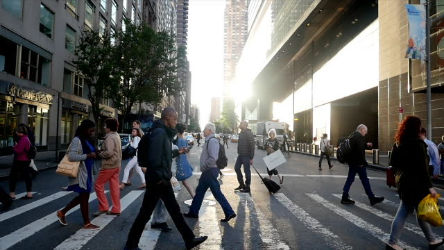 vídeos de stock, filmes e b-roll de crowd of people crossing street in new york city commuting to work. pedestrians walking background - pedestre