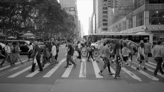 crowd of people crossing street in new york city commuting to work. pedestrians walking background