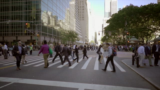 crowd of people crossing street in new york city commuting to work. pedestrians walking background
