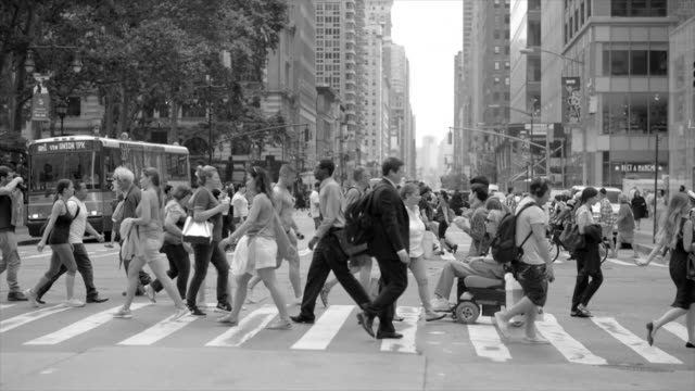 crowd of people crossing street in new york city commuting to work. pedestrians walking background - black and white stock videos & royalty-free footage