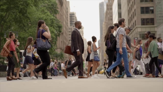 vídeos de stock, filmes e b-roll de crowd of people crossing street in new york city commuting to work. pedestrians walking background - cruzando