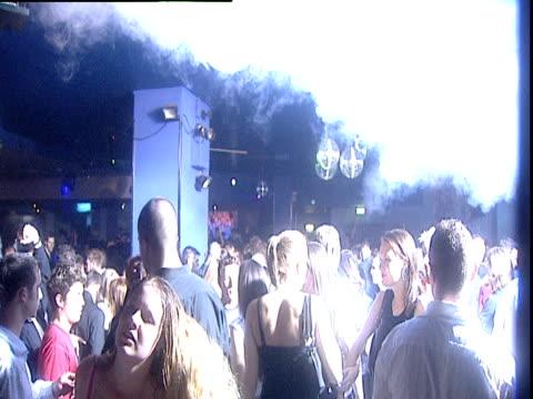 vídeos y material grabado en eventos de stock de crowd of people dance under strobe lights in nightclub uk - luces estroboscópicas