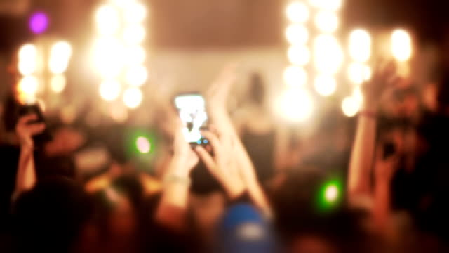 crowd of people dancing with raised arms and holding smart phones enjoying in a concert. - rhythm stock videos and b-roll footage