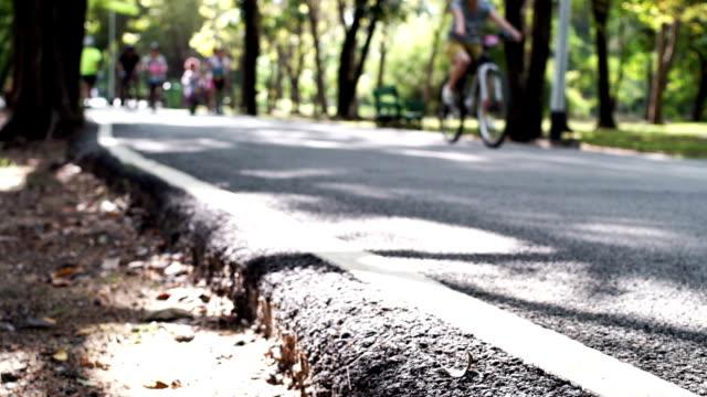群衆の人々や乗馬エクササイズ自転車公園で - アスレチック点の映像素材/bロール