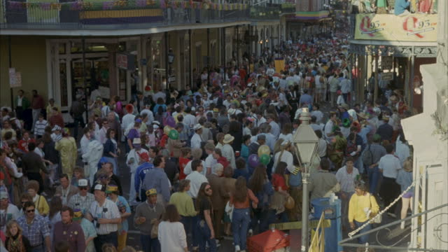 a crowd of people gather in new orleans for mardi gras. - mardi gras stock videos and b-roll footage