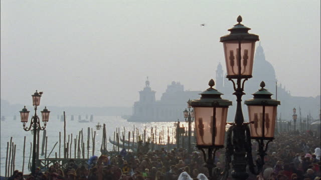 A crowd of people gather near the canal near the silhouetted Santa Maria della Salute in Venice, Italy.