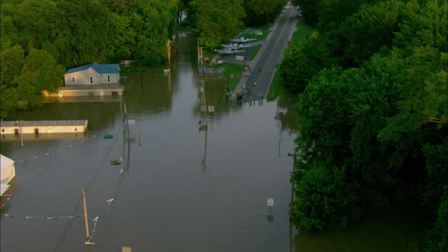vidéos et rushes de a crowd of people gather stand at the edge of a highway submerged n water. - inondation