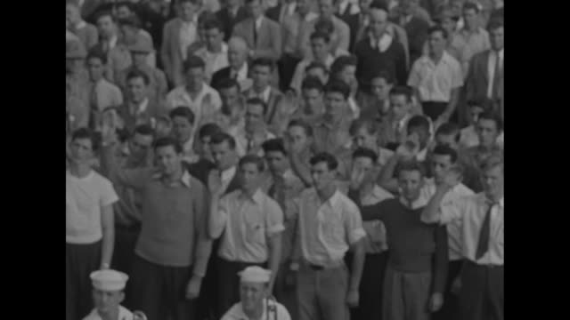 crowd of people gathered for celebration color guard behind them / closer view of people in crowd all with right hands raised / blind man arthur... - us marine corps stock videos & royalty-free footage