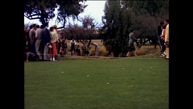 crowd of people gathered to watch bob hope play golf and runs after the ball - ボブ ホープ点の映像素材/bロール