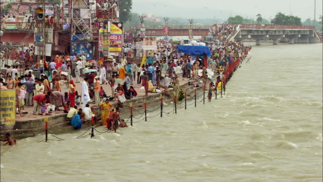 A crowd of people gathers on the banks of the Ganges River. Available in HD.