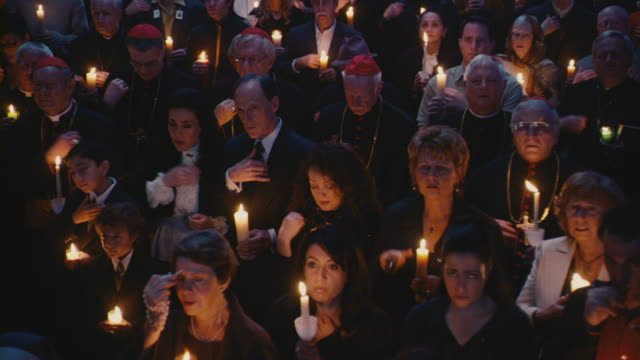 A crowd of people, holding candles, gathers to pray.