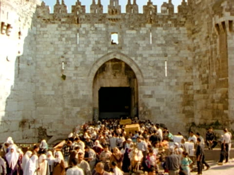 MS, crowd of people in front of gate in stone temple wall