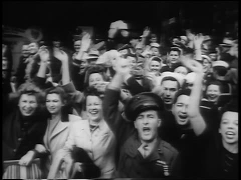 B/W 1945 crowd of people jumping up down waving smiling outdoors on VJDay