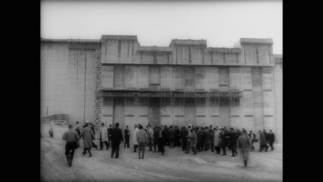 crowd of people milling around the base of the amistad dam in mexico / aerial view from helicopter overlooking the dam / lbj walking past crowd - 見渡す点の映像素材/bロール