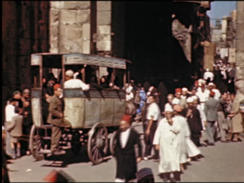 crowd of people + mule-drawn cart full of people on city street / cairo, egypt - maultier stock-videos und b-roll-filmmaterial