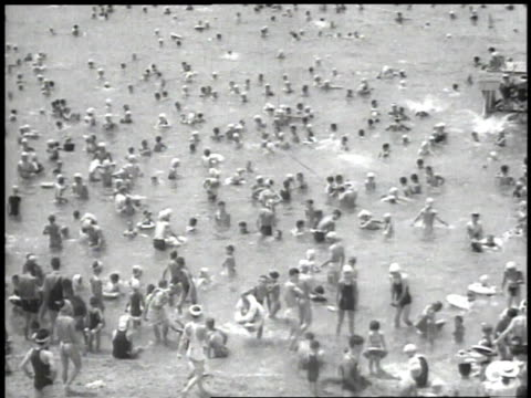 1939 MONTAGE crowd of people on beach and in the water with children playing in the sand / Japan