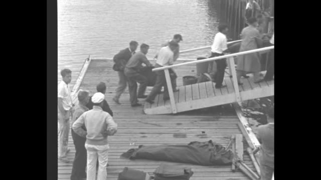 crowd of people on beach and on dock watch men carry bodies out of surf / men carry two bodies in body bags off dock up gangway to pier while other... - fluggastbrücke stock-videos und b-roll-filmmaterial