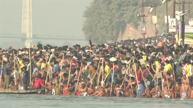 ms, crowd of people on riverbank taking ritual bath in ganges river, kumbh mela (pitcher festival), allahabad, uttar pradesh, india - スピリチュアル点の映像素材/bロール