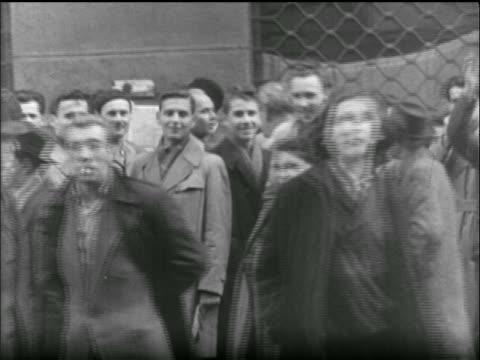 stockvideo's en b-roll-footage met b/w 1956 crowd of people on street walk look at camera / hungarian uprising - 1956
