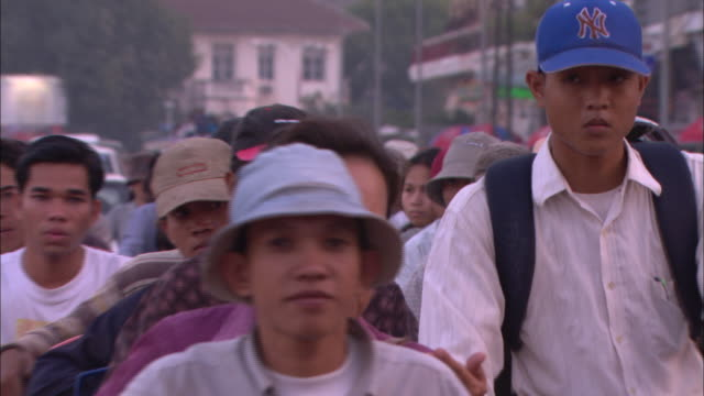 vidéos et rushes de cu, zo, ms, crowd of people riding motorized bikes and bikes in street, phnom penh, cambodia - casquette de baseball