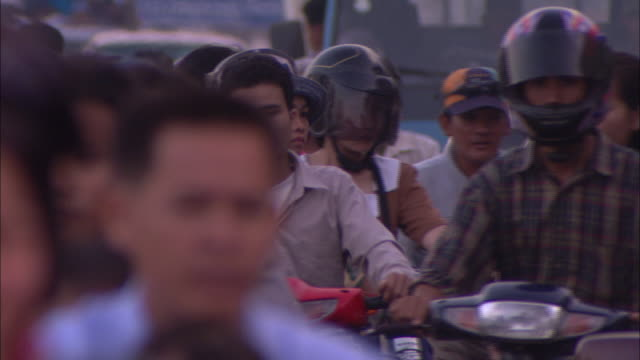 vidéos et rushes de cu, selective focus, crowd of people riding motorized bikes in street, phnom penh, cambodia - casquette de baseball