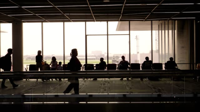 Crowd of people silhouette walking at airport terminal