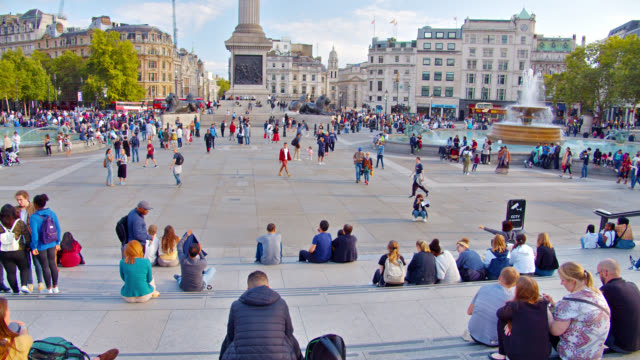crowd of people sit at rest in trafalgar square in london, uk. - editorial stock videos & royalty-free footage