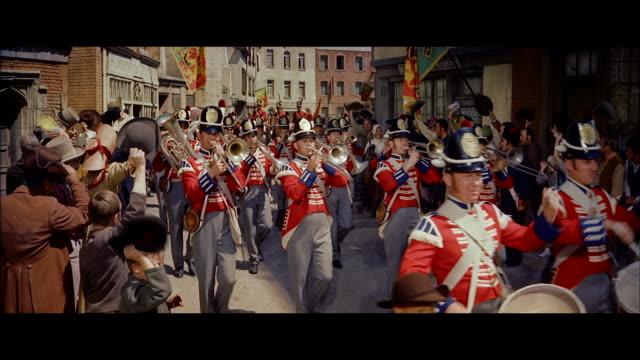 ms crowd of people standing both side of street  and british troop pasing through road - 振る点の映像素材/bロール