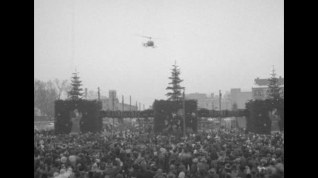 Crowd of people stands outdoors near stage and Weinachts Markt 1952 display with Christmas trees helicopter flies above / VS helicopter flying above...