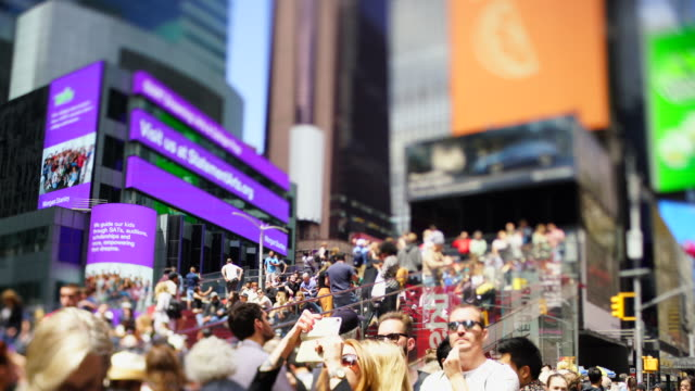 a crowd of people stays on the red steps among the glowing digital billboards at the times square at new york city ny usa on may 21 2029. - broadway manhattan stock videos & royalty-free footage
