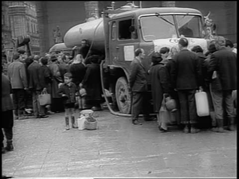 B/W 1966 crowd of people surrounding water truck after flood / Florence Italy / newsreel