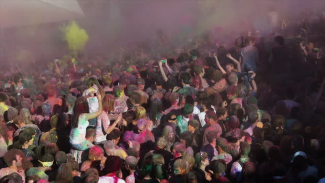 crowd of people throwing colored powder at a festival - religion stock-videos und b-roll-filmmaterial