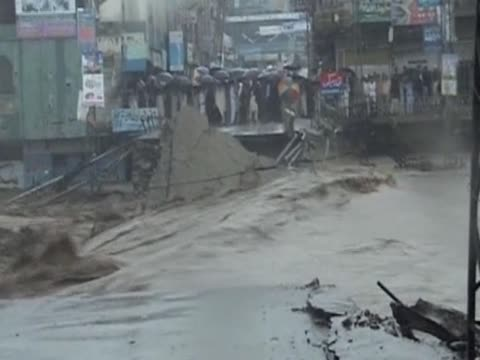 crowd of people under umbrellas stand in front of flood water in pakistan - number of people stock videos & royalty-free footage