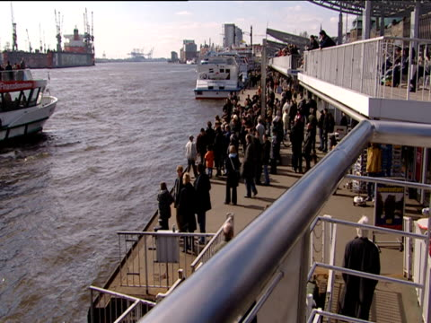 crowd of people wait on quayside to board docking ferry hamburg - ferry stock videos & royalty-free footage