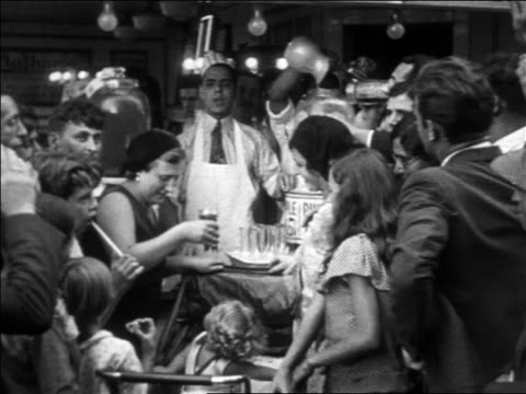 b/w 1930 crowd of people waiting in line around busy hot dog stand / coney island, nyc - coney island brooklyn stock videos & royalty-free footage