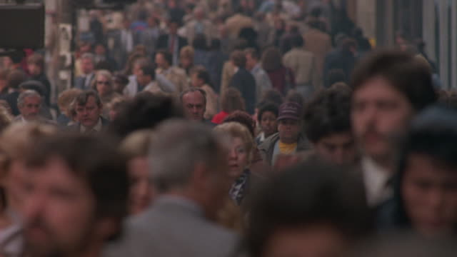 a crowd of people walk on a sidewalk in new york city. - international landmark stock videos & royalty-free footage